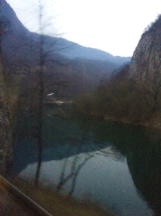 The bus travels through the Bosnian mountains as dusk falls.
