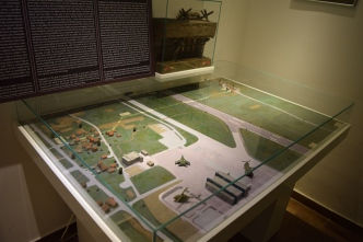 This is a model of the tunnel. You can see the airport and the runway. The white line that is painted over the fields and runway is the tunnel. The small cluster of houses in the top right of the display is where the museum is. The cluster of houses on the left is inside Sarajevo city proper.