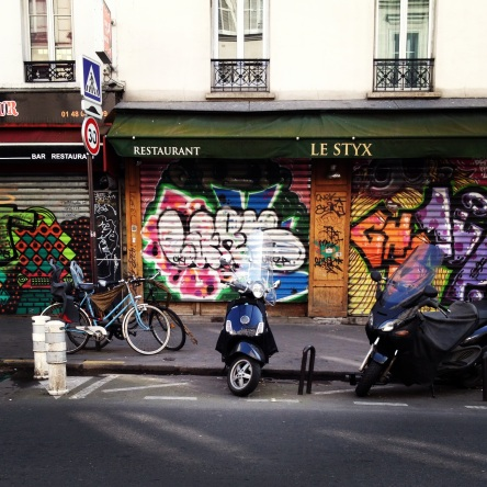 Graffiti art adds colour to the plain grey steel shutters.