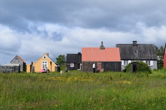 There are two employees in costume sitting in front of the yellow house. There is another museum guest standing in a white shirt in front of the red-roofed building. This shows how small these buildings were.