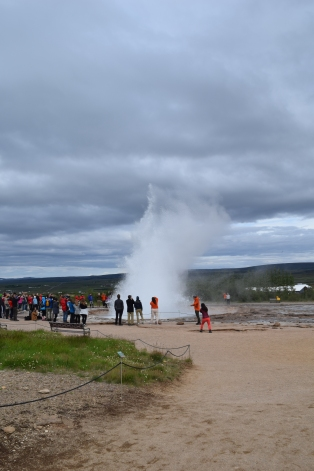 Strokkur erupts from afar.