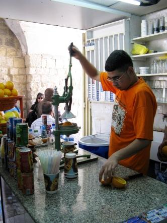 A shopkeeper makes fresh juice.
