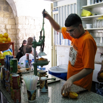 A shopkeeper makes fresh juice.