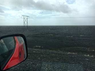 Black sand and rock stretches for kilometres to the ocean.