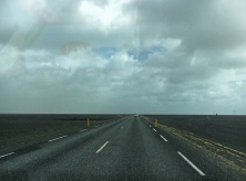 An eerie landscape. Black sand stretches on either side and it seems we are driving into the clouds.