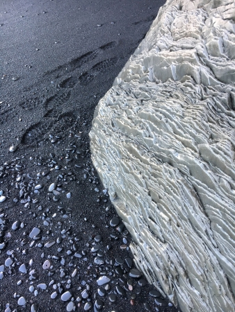 Black sand, footprints and interesting rock textures mix.